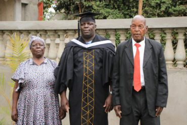 Mathew with his parents at his secondary school (high school) graduation