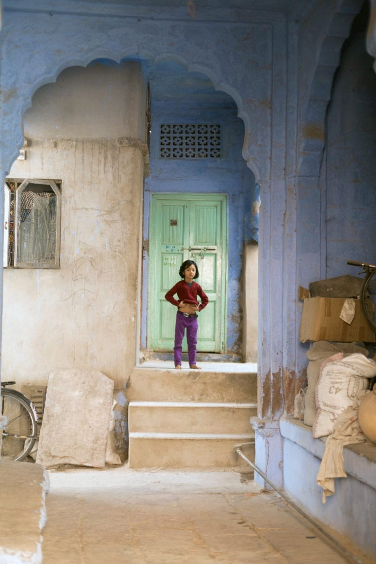A young girl stands in a blue doorway in Rajasthan, India.