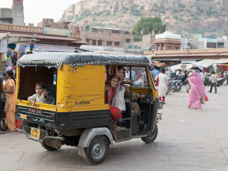 Kids look out the open side of a tuktuk in Rajasthan, India.