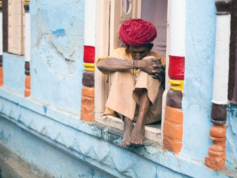 A man dressed in beige with a red turban sits in a blue window sill in Rajasthan, India.