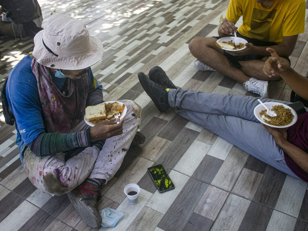 Young people who are part of the mural have lunch together and share conversation to rest a little.