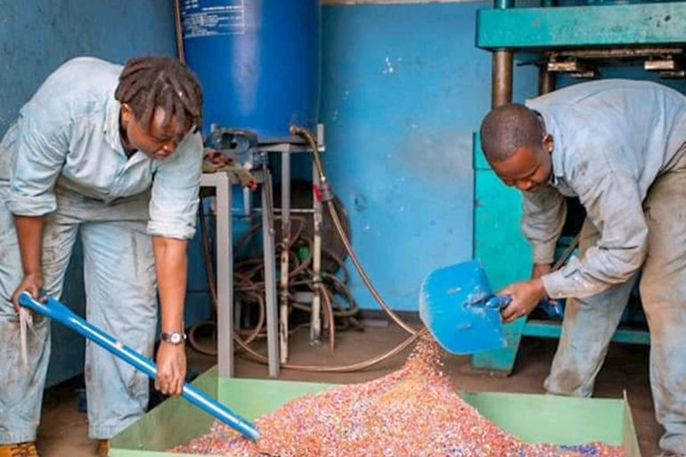 Engineers shovel plastic waste during the recycling process.