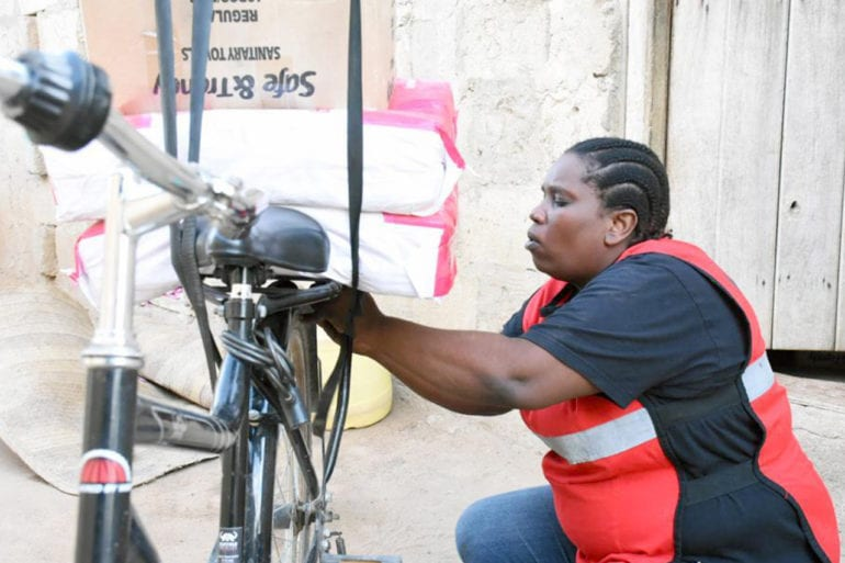 Milka Hadida getting ready to hit the road with a bicycle distributing sanitary pads