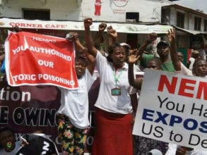 Phyllis Omido stands with her arms in the air while surrounded by Kenyan protesters.