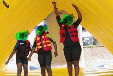A mother and two children, whose faces are blurred, play under a yellow tarp while wearing life preservers.