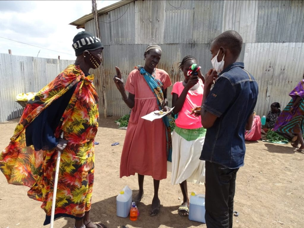 Innocent Haviyarimana stands with a group of villagers to hand out soap.